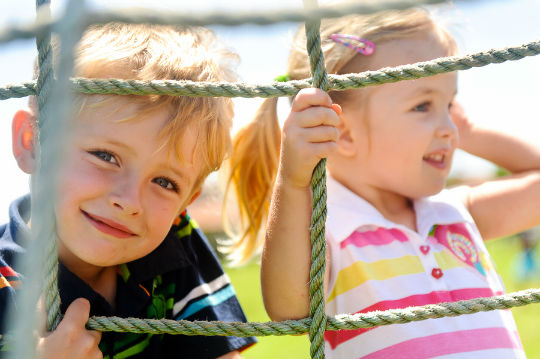 Two young children climbing a cargo net