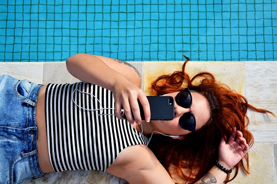 woman on phone by pool